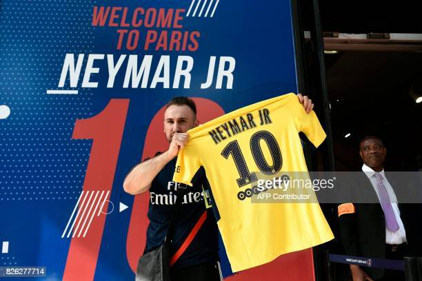 A PSG fan holds a PSG yellow away jersey marked with the number 10 and the name of Brazilian star Neymar after he purchased it from the...