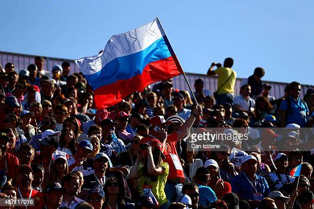 A fan holds a Russian national flag aloft during the Russian Formula One Grand Prix at Sochi Autodrom on October 12 2014 in Sochi Russia