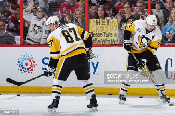 A fan holds a sign as Sidney Crosby and Evgeni Malkin of the Pittsburgh Penguins skate during warmups prior to a game against the Ottawa Senators in...