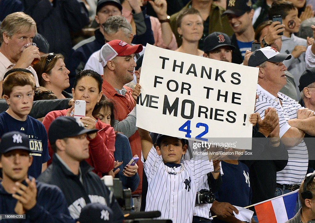 A fan holds a sign in honor of Mariano Rivera #42 of the New York Yankees before a game against the Boston Red Sox on September 15, 2013 at Fenway Park in Boston Massachusetts.