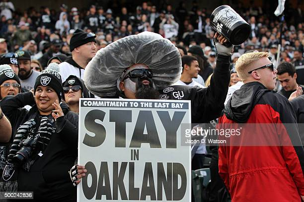 A fan holds a sign in the stands imploring the team to stay in Oakland during the NFL game between the Oakland Raiders and the Kansas City Chiefs at...