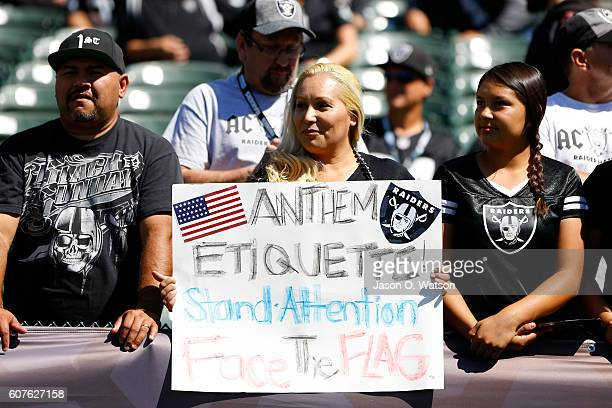 A fan holds a sign in the stands in reference to national anthem protests by players prior to the NFL game between the Oakland Raiders and the...