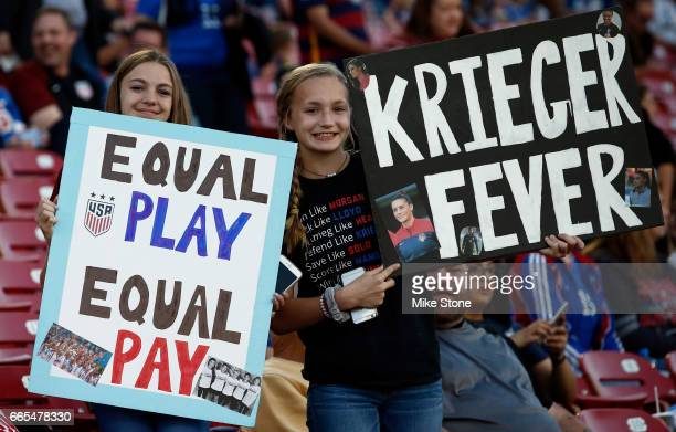 A fan holds a sign referencing wage equality before the the International Friendly soccer match between Russia and the US at Toyota Stadium on April...