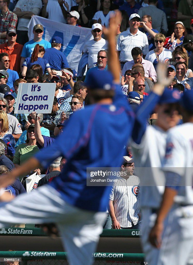 A fan holds a sign saying 'It's Gonna Happen' as members of the Chicago Cubs celebrate a win over the Washington Nationals at Wrigley Field on May 6, 2016 in Chicago, Illinois. The Cubs defeated the Nationals 8-6.