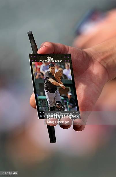 A fan holds a trading card featuring Chris Iannetta of the Colorado Rockies as he pursues autographs prior to the Rockies facing the San Diego Padres...