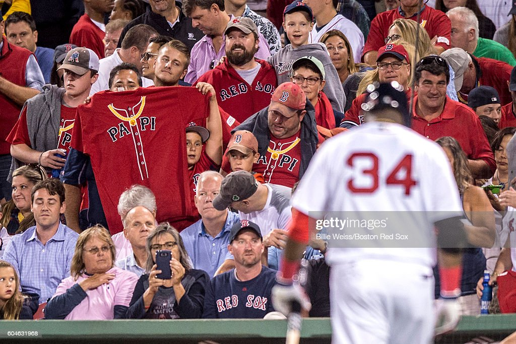A fan holds a T-shirt as David Ortiz #34 of the Boston Red Sox walks to the dugout after striking out during the seventh inning of a game against the Baltimore Orioles on September 13, 2016 at Fenway Park in Boston, Massachusetts.
