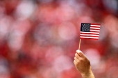 A fan holds an American flag during the singing of the National Anthem before the San Francisco 49ers' season opener against the Seattle Seahawks at...