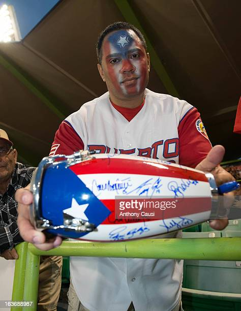 A fan holds an autographed bongo drum signed by Team Puerto Rico before Pool C Game 2 between Spain and Puerto Rico in the first round of the 2013...