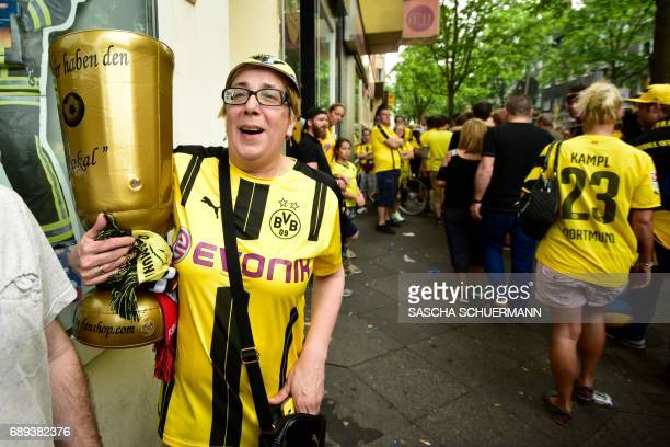 A fan holds an inflatable trophy as Borussia Dortmund players arrive at Borsigplatz during celebrations after winning the German Cup final in...