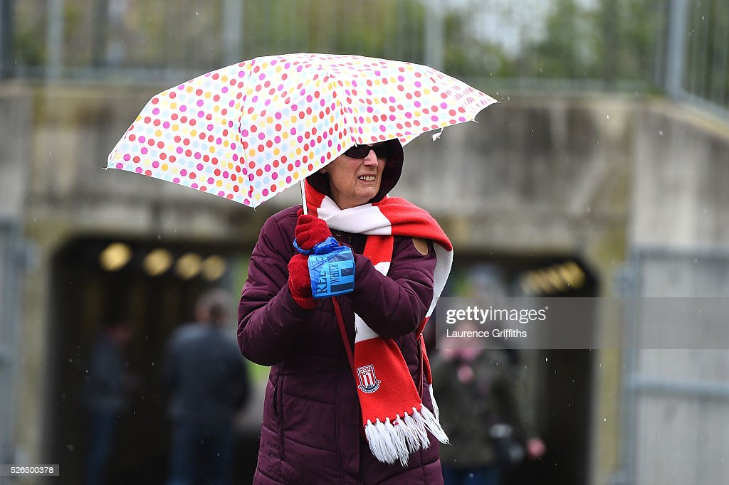 A fan holds her umbrella on her way to the stadium prior to the Barclays Premier League match between Stoke City and Sunderland at the Britannia Stadium on April 30, 2016 in Stoke on Trent, England.