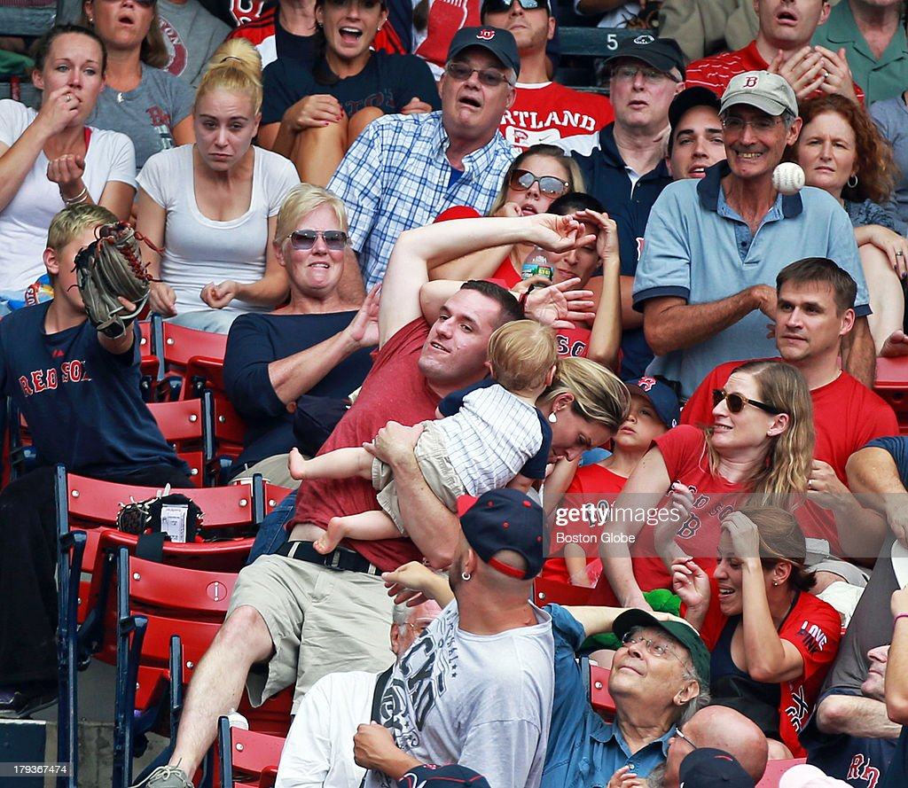 A fan holds on to a baby with one hand and tries to catch a foul ball with the other. The Boston Red Sox hosted the Chicago White Sox in a regular season MLB game at Fenway Park.