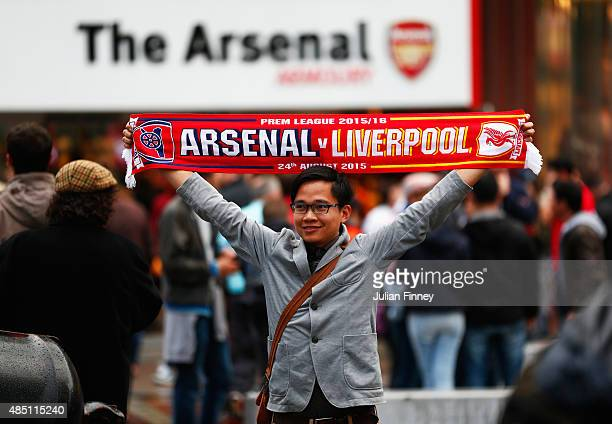 A fan holds the match scarf outside the ground prior to the Barclays Premier League match between Arsenal and Liverpool at Emirates Stadium on August...