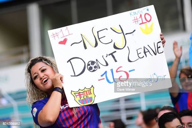 A fan holds up a banner begging Neymar Jr of Barcelona to stay at the club during the International Champions Cup match between Barcelona and Real...