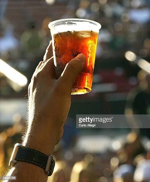 A fan holds up a beer during this stop of Lollapalooza at the Verizon Amphitheatre in Irvine California August 16 2003 Lollapalooza is a multi act...