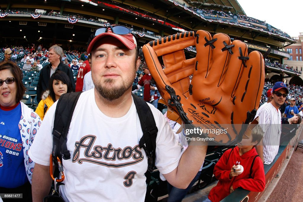 A fan holds up a giant baseball glove before a game between the Chicago Cubs and the Houston Astros on Opening Day on April 6, 2009 at Minute Maid Park in Houston, Texas.