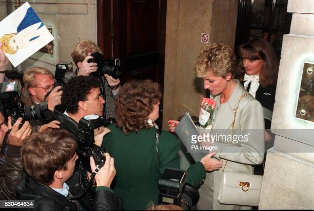 A fan holds up a picture of the Princess of Wales as she and her friend Catherine Soames are mobbed by wellwishers and photographers on leaving the...