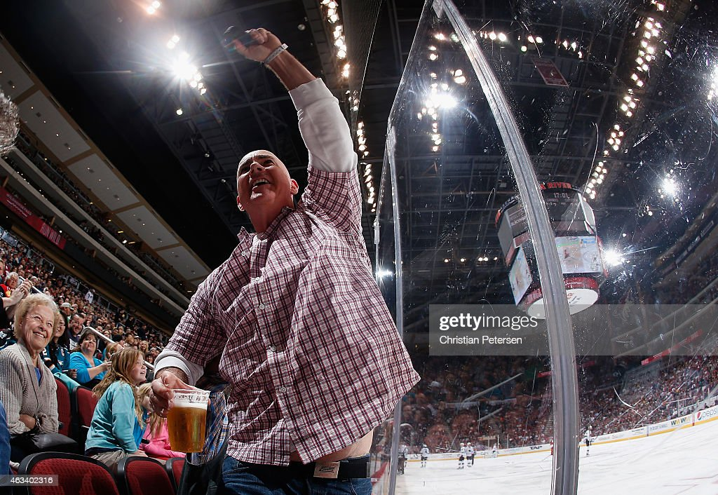 A fan holds up a puck that stuck him in the head during the third period of the NHL game between the Arizona Coyotes the San Jose Sharks at Gila River Arena on February 13, 2015 in Glendale, Arizona.
