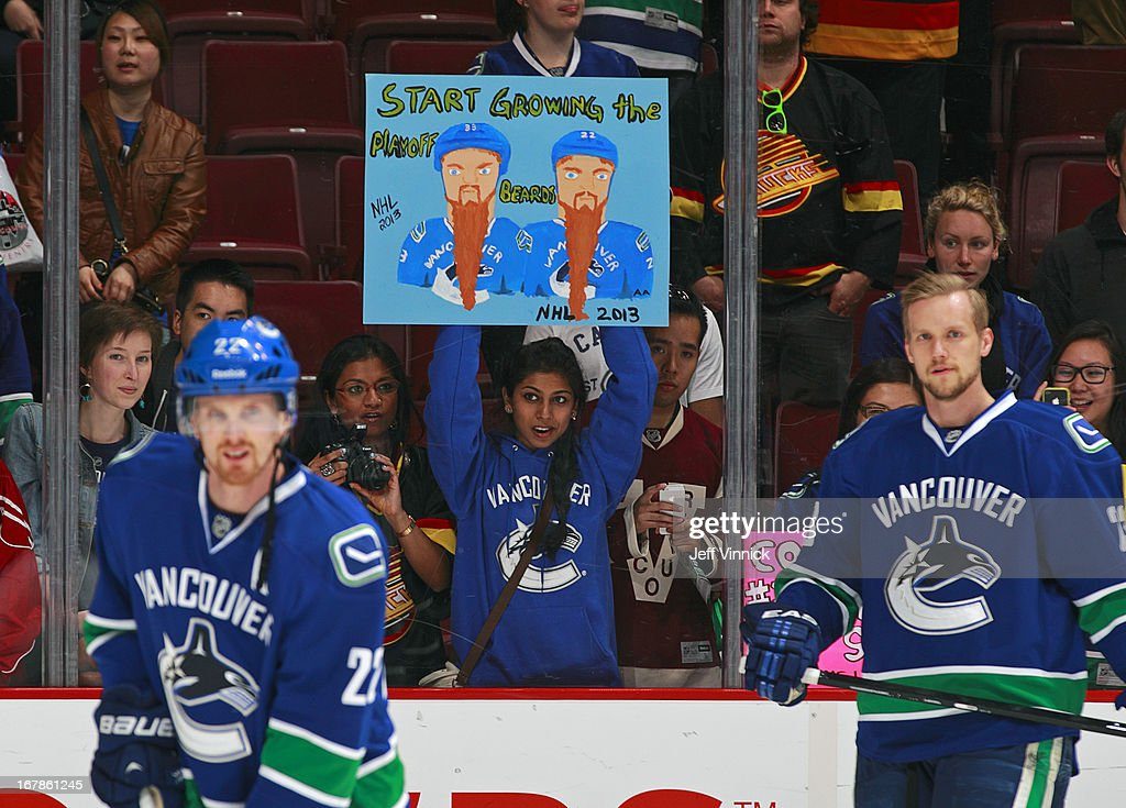 A fan holds up a sign in front of Daniel Sedin #22 and Alexander Edler #23 of the Vancouver Canucks during their NHL game against the Anaheim Ducks at Rogers Arena April 25, 2013 in Vancouver, British Columbia, Canada. Anaheim won 3-1.