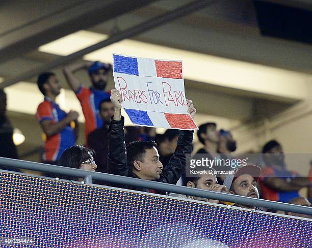 A fan holds up a sign in honor for the victims of the terrorist attacks in Paris during the final game of a threematch three city Twenty20 series US...