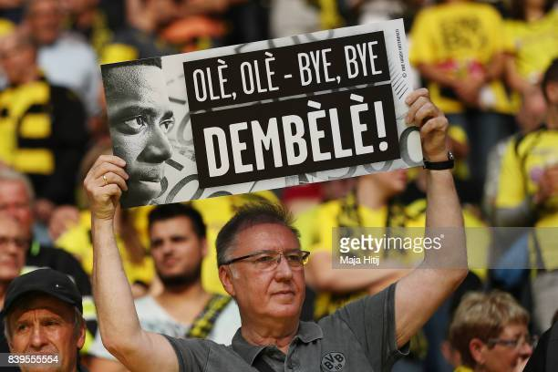 A fan holds up a sign in response to Dortmund's Ousmane Dembele's departure ahead of the Bundesliga match between Borussia Dortmund and Hertha BSC at...
