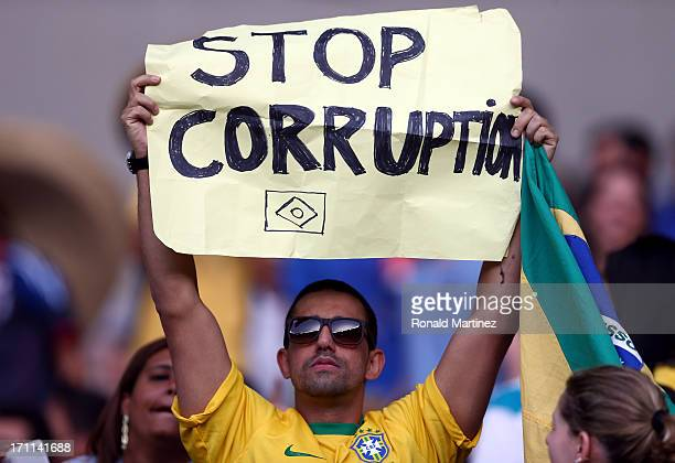 A fan holds up a sign reading 'Stop Corruption' during the FIFA Confederations Cup Brazil 2013 Group A match between Japan and Mexico at Estadio...