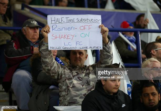 A fan holds up a sign saying Ranieri off Shakey on in reference to Craig Shakespeare manager / head coach of Leicester City during the UEFA Champions...