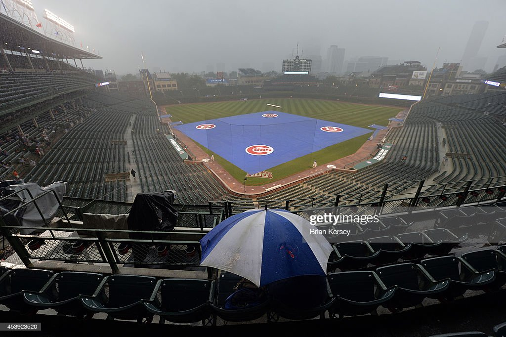 A fan huddles under an umbrella as rain falls, delaying the restart of a suspended game from August 19 between the Chicago Cubs and the San Francisco Giants at Wrigley Field on August 21, 2014 in Chicago, Illinois. The game was initially called off in the early morning hours of August 20, but Major League Baseball accepted the Giants' appeal, ruling the delay was caused by a mechanical failure of the tarp and changing the status of the game from cancelled and completed with a Cubs 2-0 win to a suspended game. The Cubs and Giants hope to finish the game before their regularly scheduled game today.