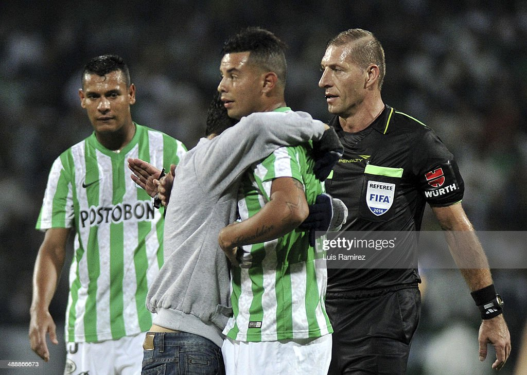 A fan huges Edwin Cardona of Atletico Nacional after got into the field during a quarter final match between Atletico Nacional and Defensor Sporting as part of Copa Bridgestone Libertadores 2014 at Atanasio Girardot Stadium on May 08, 2014 in Medellin, Colombia.