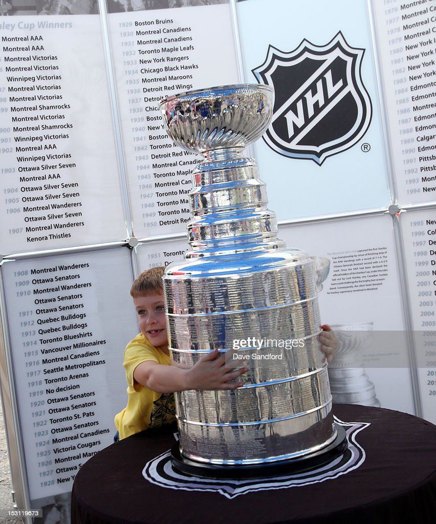 A fan hugs the Stanley Cup on display for the Fun Fair at the Stirling and District Recreation Centre during Kraft Hockeyville Day 1 on September 30, 2012 in Stirling, Ontario, Canada.