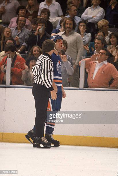 A fan in a cardigan sweater shouts at Canadian professional hockey player Dave Semenko of the Edmonton Oilers who has a bloody face after a fight...