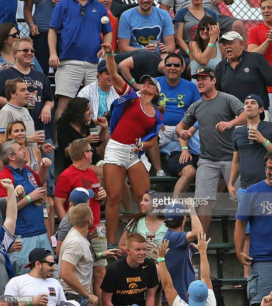 A fan in the left field bleachers throws back a home run ball hit by Salvador Perez of the Kansas City Royals during a game against the Chicago Cubs...