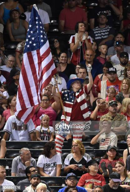 A fan in the left field bleachers wears red white and blue clothes while waving an American Flag during a game between the Arizona Diamondbacks and...