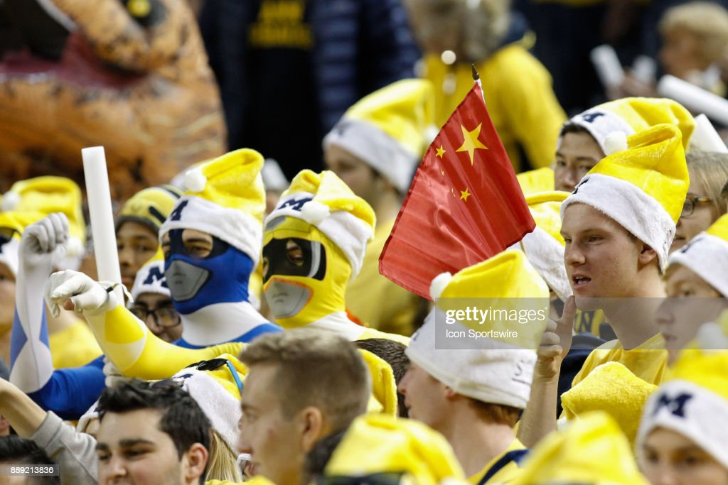 A fan in the Michigan student section waves a flag of the People's Republic of China before the start of a regular season non-conference basketball game between the UCLA Bruins and the Michigan Wolverines on December 9, 2017 at the Crisler Center in Ann Arbor, Michigan. Michigan defeated UCLA 78-69 in overtime.