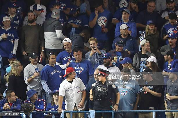 TORONTO ON OCTOBER 4 A fan in the outfield have words a Toronto Police officer after one threw a beer can at Baltimore Orioles left fielder Hyun Soo...