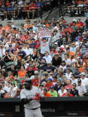 A fan in the seats along the firstbase line stands up with a sign reading 'Big Cheater' as designatedhitter David Ortiz of the Boston Red Sox steps...
