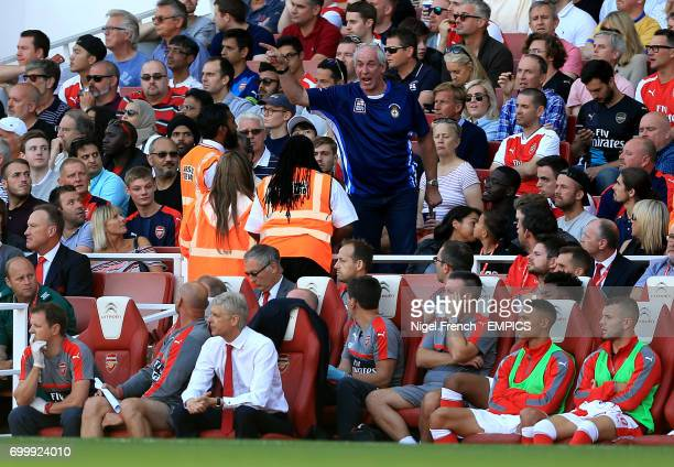 A fan in the stands exchanges words with stewards as Arsenal manager Arsene Wenger sits in the dugout