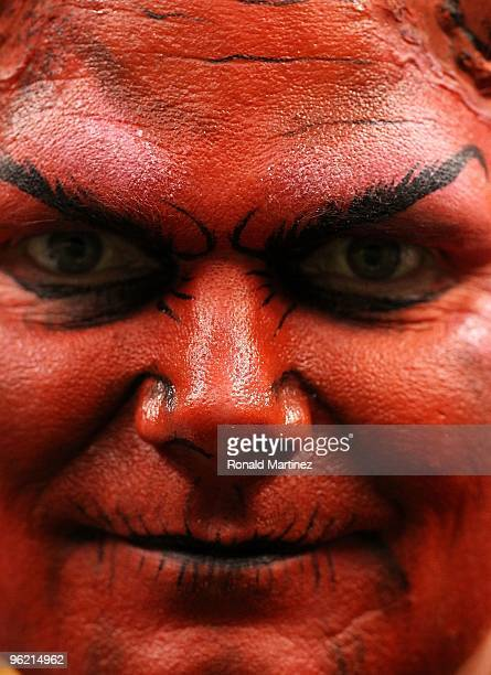A fan in the stands is seen with red paint on his face to look like the devil during the NFC Championship Game between the New Orleans Saints and the...