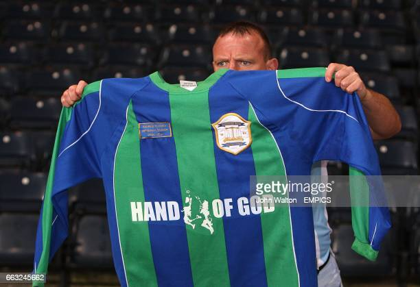 A fan in the stands poses wiht a shirt advertising the infamous hand of God