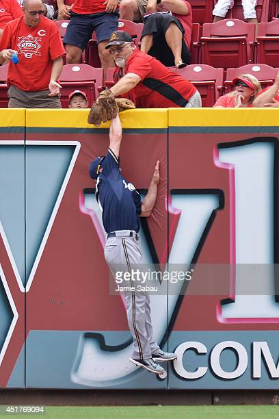 A fan interferes with an attempt by Logan Schafer of the Milwaukee Brewers to catch a long ball hit by Ramon Santiago of the Cincinnati Reds in the...