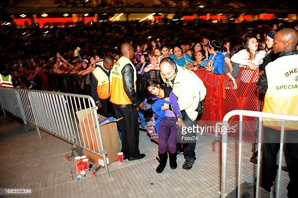 A fan is assisted by security a guard during the Justin Bieber concert at the Cape Town Stadium on May 8 in Cape Town South Africa On his 'Believe'...