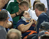 A fan is carried out by medics after getting hit in the side of her head by a foul ball in the eighth inning during a MLB game between the Detroit...