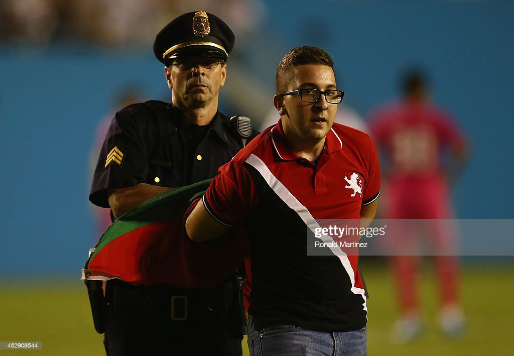 A fan is detained by a police officer after running on the field during a Guinness International Champions Cup 2014 match between AS Roma and Real Madrid at Cotton Bowl on July 29, 2014 in Dallas, Texas.