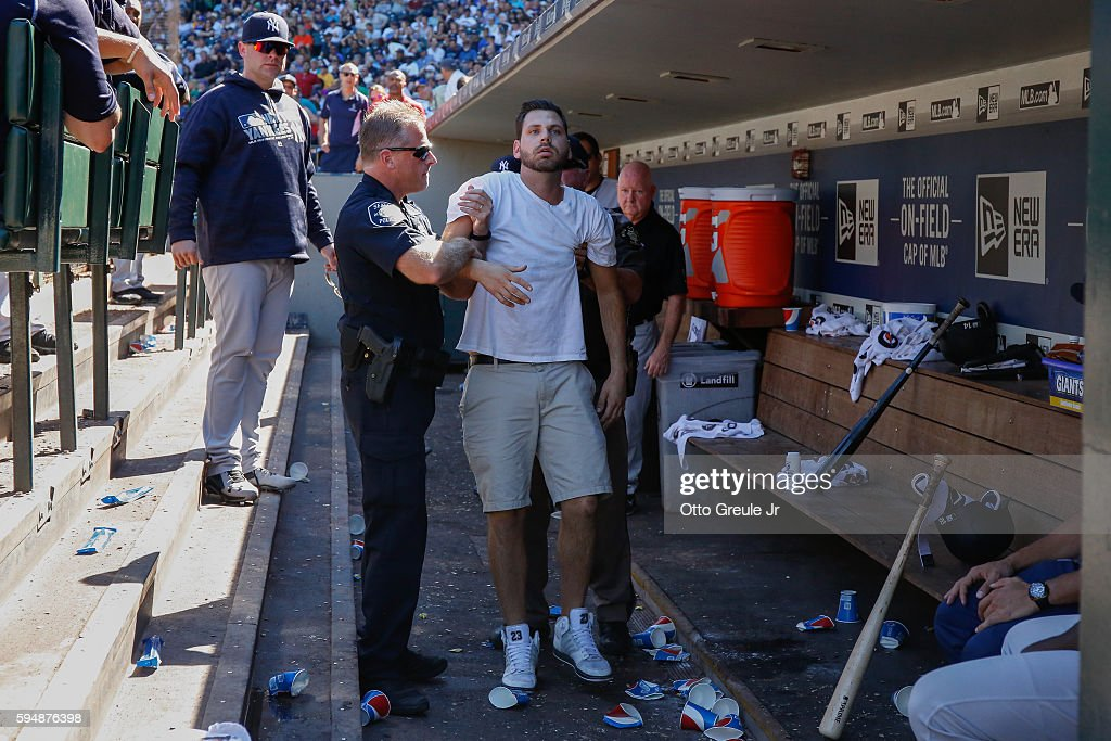 A fan is escorted by police out of the New York Yankees dugout after climbing onto its roof stumbling and falling into the dugout during the game...