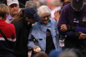 A fan is escorted from the seating bowl after being struck by a foul ball as the San Francisco Giants face the Colorado Rockies at Coors Field on May...