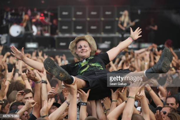 A fan is held up by fellow fans as he floats towards the stage at the Hammerfall performance at the 2014 Wacken Open Air heavy metal music festival...