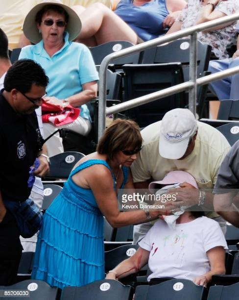 A fan is helped by the medical staff after getting hit in the face by a foul ball off the bat of Kelly Shoppach of the Cleveland Indians during a...