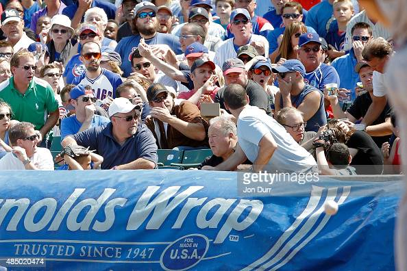 A fan is hit by a foul ball during the game between the Chicago Cubs and the Atlanta Braves at Wrigley Field on August 23 2015 in Chicago Illinois