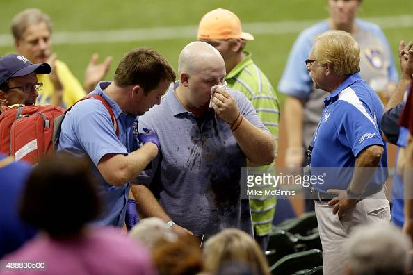A fan is led away after beinghit by a foul ball off the bat of Matt Holliday of the St Louis Cardinals during the seventh inning against the...