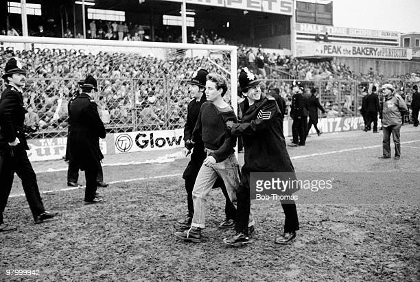 A fan is removed from The Baseball Ground Derby after the FA Cup 5th Round match between Derby County and Manchester United on 19th February 1983...