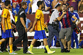 A fan is restrained by a police officer after he ran onto the field and neared Luis Suarez of Barcelona following their loss to Chelsea during the...